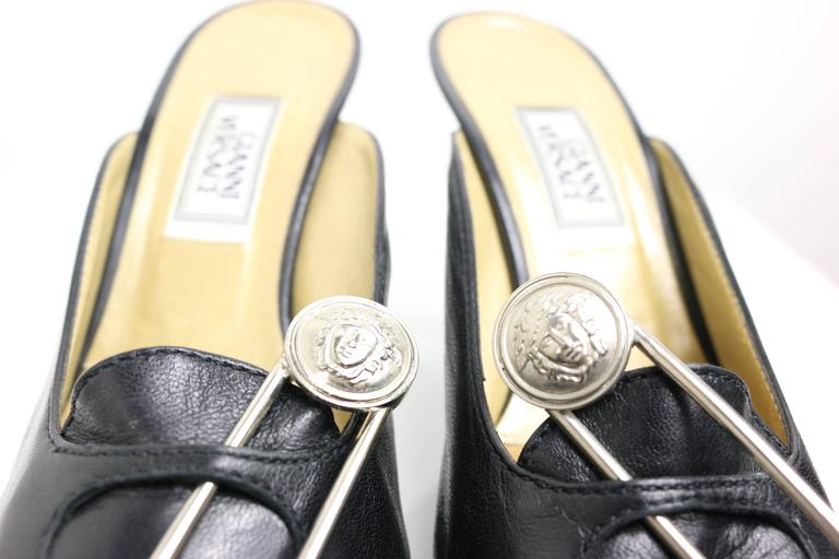 - Gianni Versace black leather iconic medusa safety pins mules from 1994 collection. 