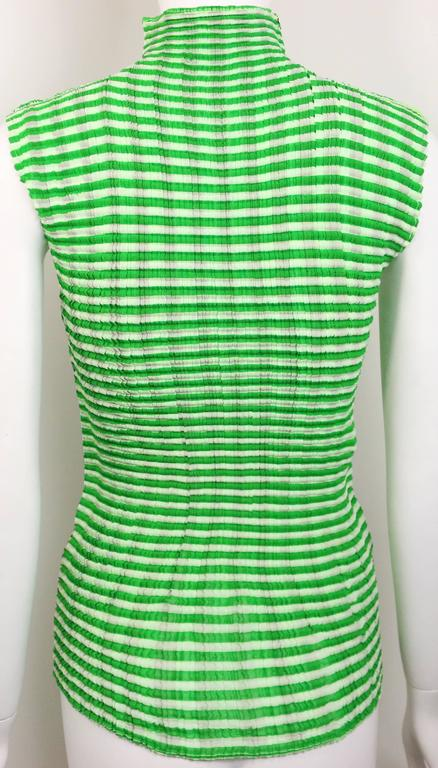 - Issey Miyake pleated two sides( one side is black vertical stripe, white and yellow horizontal stripe. The other side is white and green horizontal stripe) colour block sleeveless top.   - Size M.   - 100% Polyester.   - Made in Japan.   - Height:
