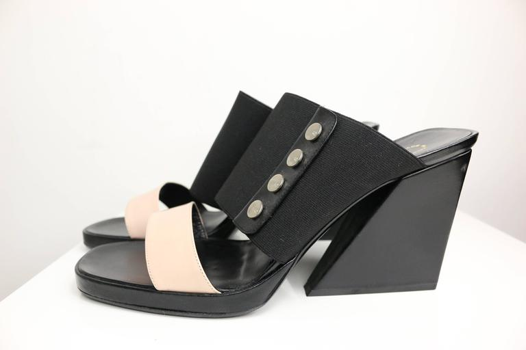 "- Chanel bi tone light pink leather strap, black elastic band strap wedge shoes.   - Featuring four ""CC"" logo panel metal studs on each wedge.   - Made in Italy.   - SIze 38.   - Height: 4in, Length: 8in ( measurements are approximate)."