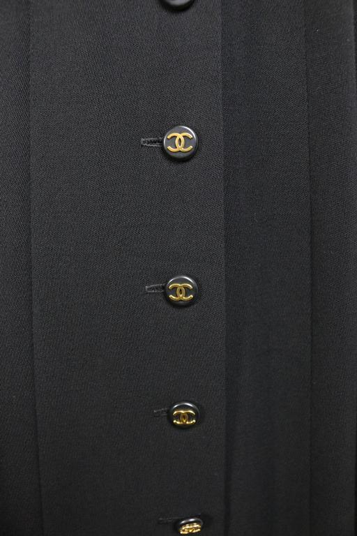 """- Vintage Chanel black wool A-Line long skirt from 1994 collection.   - Featuring ten front panel gold """"CC"""" logo buttons and two side pockets.   - Size 38.   - 100% Wool, 100% Silk double lining."""