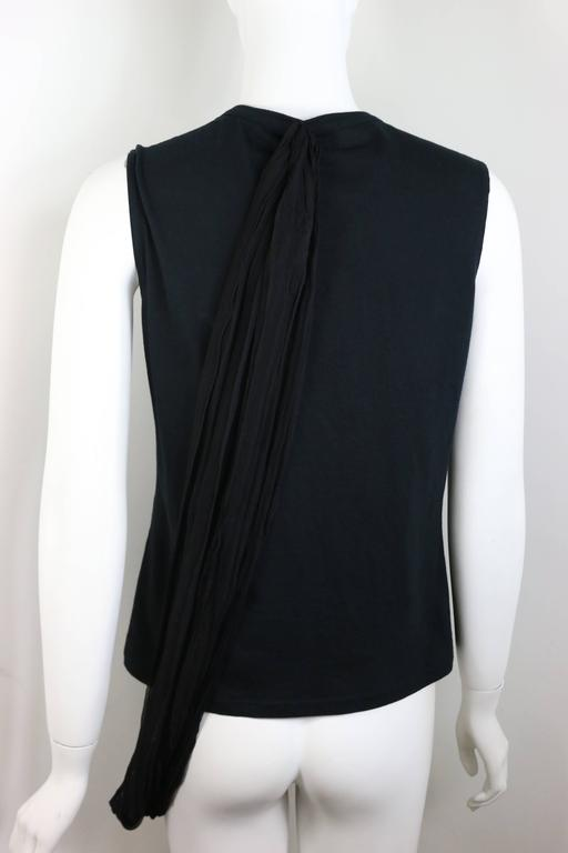 - This Dior black tank top from early 2000s John Galliano. It has a black silk wrapping details connected from the bottom front to the back top. You can play around the wrap the way you want wrapping around your body.   - Size 42 FR, USA 10.   -
