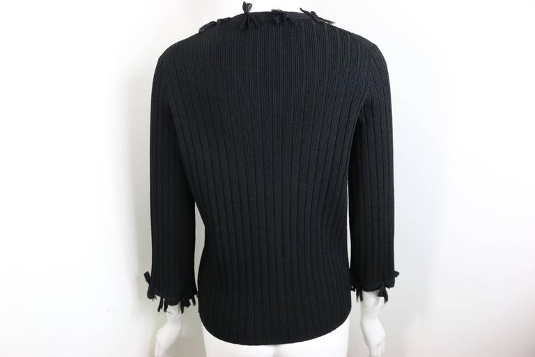 - Chanel black knitted silk bow trim three-quarter sleeve cardigan from 2006 pre collection. 