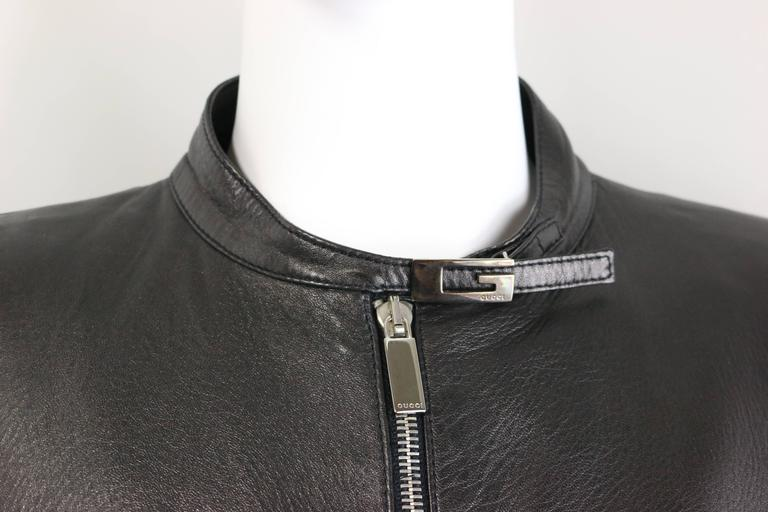 """- Gucci by Tom Ford black lambskin leather jacket from Fall 1996 collection. This is a truly collectable item!   - Featuring silver logo """"G"""" on the neck, two cuffs and hem closing. Front silver zipper closing. This leather jacket has"""
