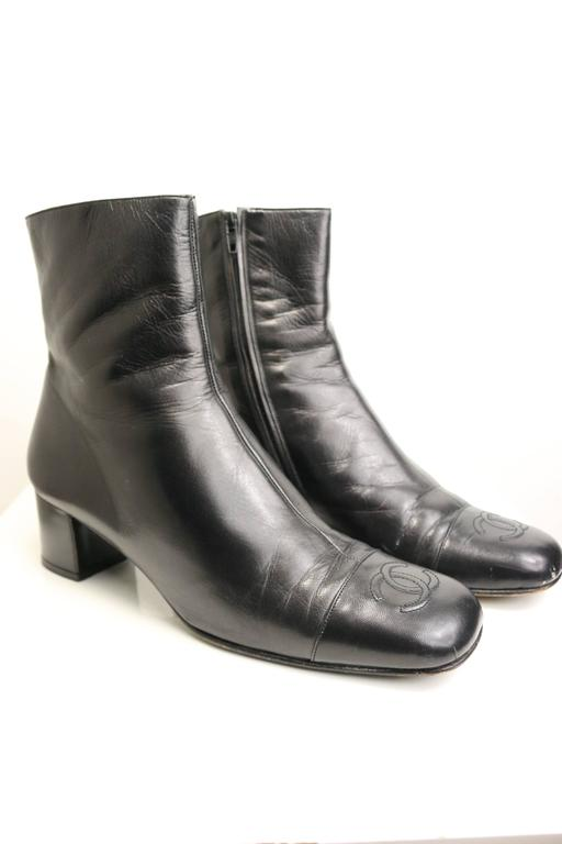 """- Vintage 90s Chanel black leather square toe """"CC"""" logo ankle boots. This item is chic, durable and highly collectable.   - Made in Italy.   - Size 38.5."""