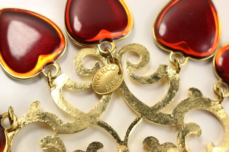 - Vintage 80s Nina Ricci red hearts gold toned setting statement clip on earrings. Featuring  gold toned heart shaped patterns attached with five red hearts dropping on each earring. This is one of a kind design! Its chunky, its chic and its a