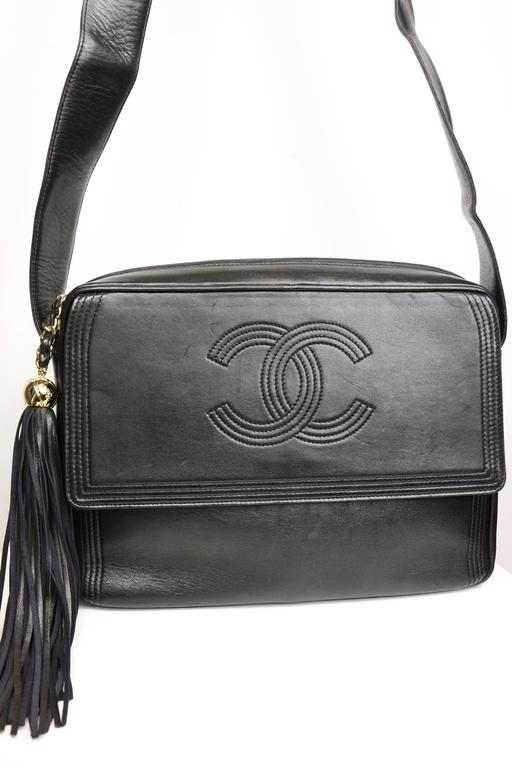 - Vintage 90s Chanel black leather flap bag with tassel.   - Featuring a