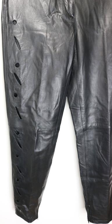 - Vintage 90s Istante by Gianni Versace black leather with cutout pattern pants. It is a slim tapped leg cut style.    - Featuring right leg front, left leg back and back pockets cutout patterns.  Zipper on the bottom inner leg hem.   - Made in