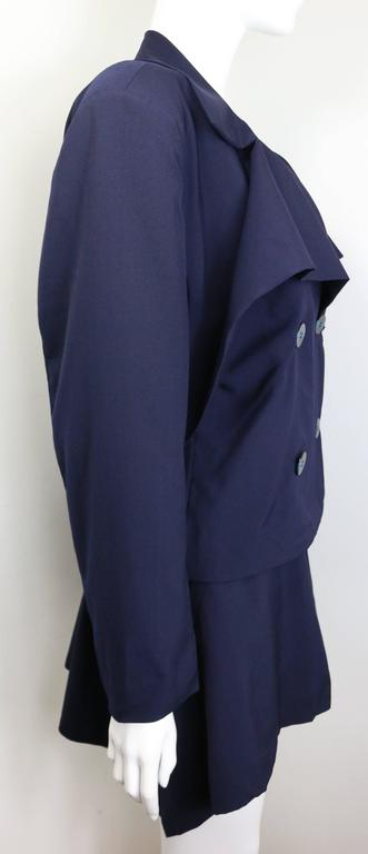 - Vintage 80s Issey Miyake navy blue double breasted jacket and skirt ensemble.   - Jacket: Four front black with blue stripe buttons fastening. Wide collars. Back strap with two black blue stripe buttons.   - Skirt: Irregular hem skirt with four