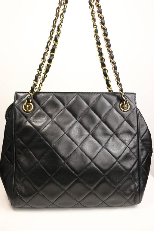 "- Vintage 90s Chanel black quilted lambskin leather petite timeless shoulder strap tote. Featuring a gold toned leather chain double straps and a snap button with gold toned ""Chanel"" zipper closure. The interior has one zipper pocket and"