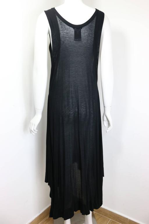 - Ann Demeulemeester black asymmetrical long dress. Featuring medium weight see through fabric with asymmetrical hem. Her signature style has always been consistently dark with a rock and roll touch in it. Timeless and unique!   - Made in Italy.   -