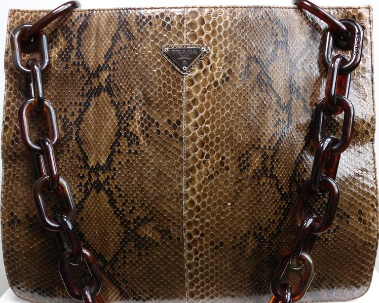 - Vintage 90s Prada python tote bag with plastic tortoiseshell shoulder strap. This exotic and chic tote bag is beautifully constructed from python giving it a neutral colouring.   Featuring a python front and back exterior with brown polyester