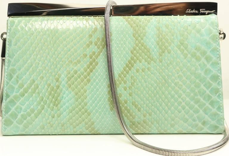 - Vintage 90s Salvatore Ferragamo green python clutch with silver toned detachable shoulder strap. Featuring an interior zipper pocket. This erotic python clutch is suitable for causal daily use or an evening night out.  - Made in Italy.   - Length: