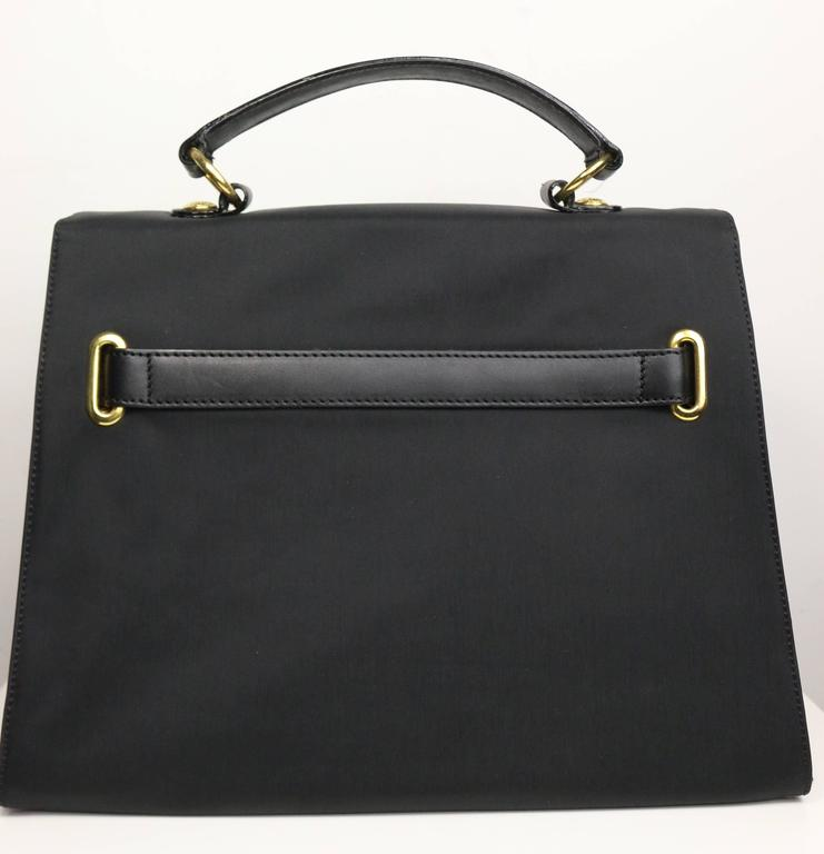 - Vintage 90s Moschino black nylon kelly style bag. This bag is made in Italy by RedWall. Featuring a gold hardware interlock closure, black leather handle and interior