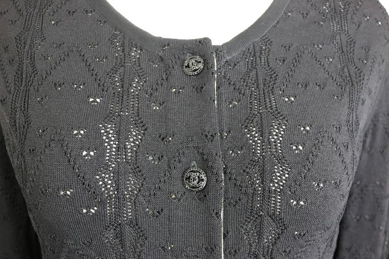 "- This is a cardigan sweater by Chanel, from 2008 pre collection.  This sweater features a black crochet knit in heart pattern and a horizontal stripe ruffle bottom. Featuring six shiny black rhinestones ""CC"" front buttons closure with"