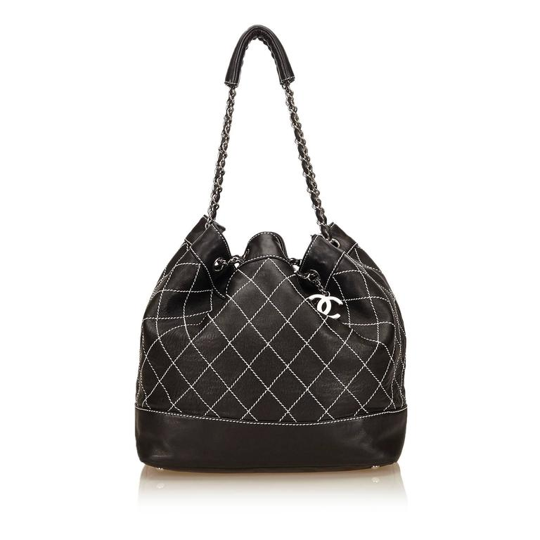 - This Chanel black and white wild stitch drawstring shoulder tote bag featuers a leather body, a silver-tone hardware, and an interior zip pocket. The bag has silver eyelets through which silver chain link straps are threaded and has leather