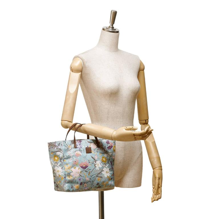 - This Gucci blue multi coloured tote bag features a floral printed canvas body, flat leather handles, open top, and interior slip pocket.   - Made in Italy.   - Size: 24cm x 21cm x 10cm.   - Include: Dust bag.   - Condition: Excellent.