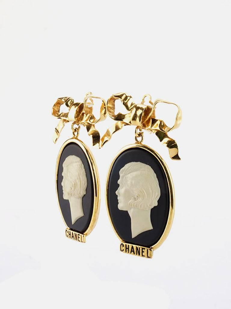 - Vintage Chanel gold plate bow with dangle white statue clip on earrings. This earrings is really rare and beautifully made. A museum piece!!!   - Made in France.  - Size: W 5.2cm × H 8 cm.   - Include: Original Box.