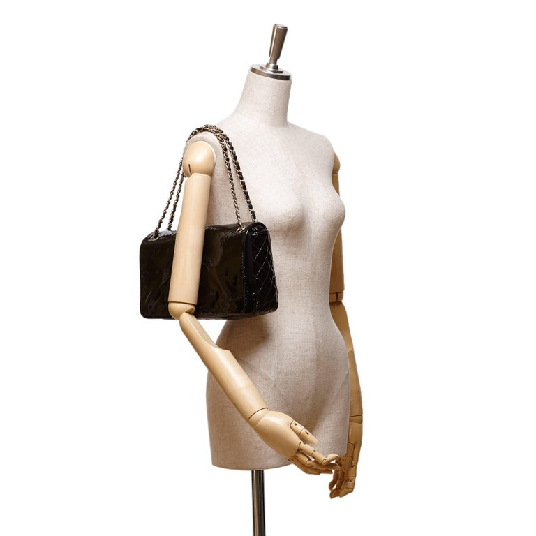 """- This Chanel """"CC"""" logo flap shoulder bag features a black patent leather body, flat leather handle with gold-tone chain details, front flap with magnetic closure, and interior zip pocket.  - Made in France.   - Size: 29.5cm x 18cm x 6cm. Shoulder"""