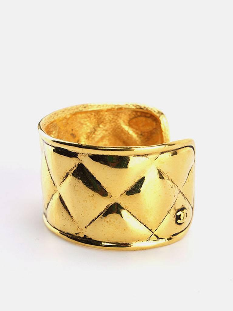 - Vintage 90s Chanel gold toned plate quilted wild cuff bangle. Unique and elegant to wear it with your casual wear or an evening night out.   - Made in France.   - Inner diameter: 6.5 x 5.5 cm (2.56 x 2.17 inches).   - Outer circumference: 20.5 cm