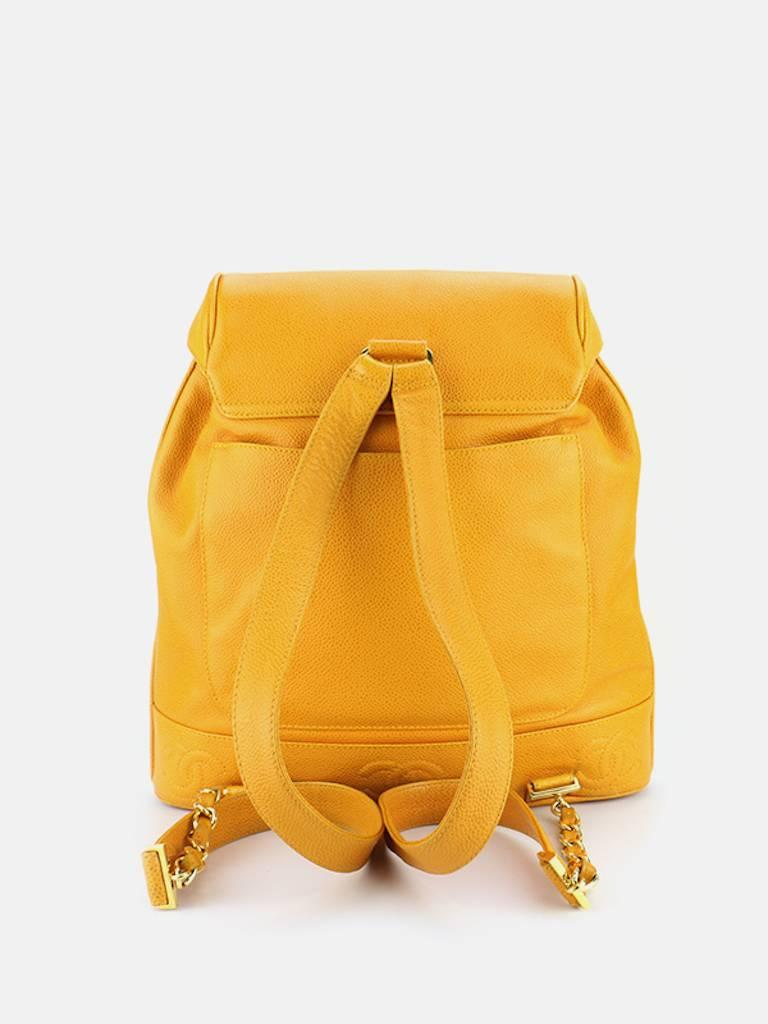 "- Vintage 90s Chanel Orange caviar leather Backpack with pouch. Featuring a gold toned ""CC"" interlock hardware flap with drawstring closure. A slip pocket on the back, an interior zipper pocket. This Chanel orange backpack is one of a"