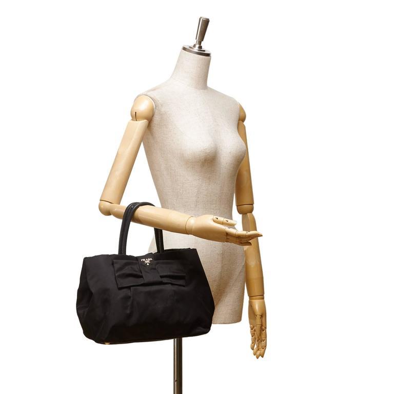 b1306cc3202c This Prada black Tessuto bow tote bag features a black nylon body, rolled  leather