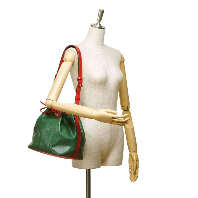 - This vintage 1994 Louis Vuitton petit noe features a green and red epi leather, an adjustable flat strap, an open top with a drawstring closure, and Alcantara lining. Rare and interesting colour combination Louis Vuitton shoulder bag!  - Made in