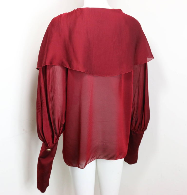 - Chanel red silk long sleeve victorian style long sleeves shirt from 2007 A/W collection.   - Two silk layers.   - Top three buttons closure.   - Thirteen buttons closure on the sleeves.   - Size 40.   - 100% Silk.