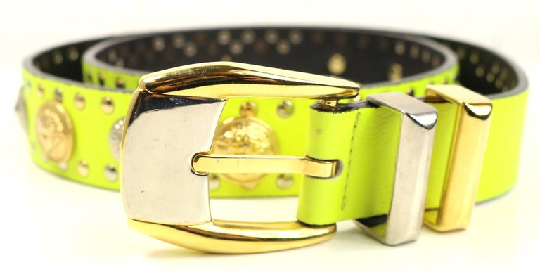 - Vintage 90s Gianni Versace neon green/yellow lambskin leather with gold and silver studs belt.   - Featuring embedded gold toned Medusa and silver toned shield studs.   - Gold and silver toned hardware buckle fastening.   - 37 inches long and 1.5