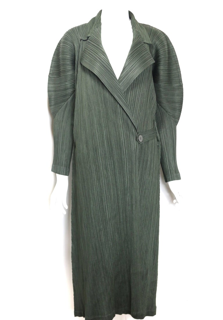 - Vintage 90s Issey Miyake Pleats Please green pleated long belted coat.   - Sculptural shoulder.   - Strap with button closure.   - Size 3. (M).   - 100% Polyester.
