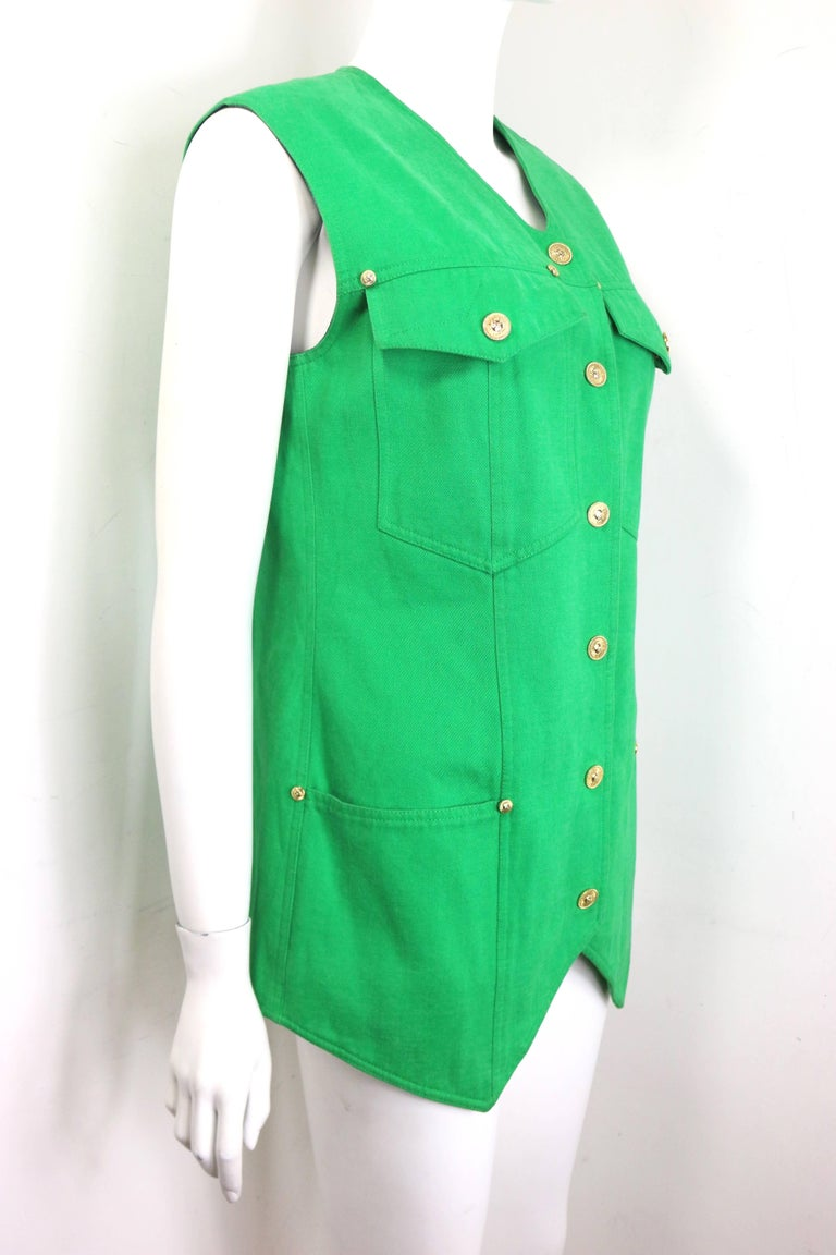"""- Vintage 90s Gianni Versace Jeans Couture green cotton collarless vest.   - Embedded with gold toned """"Sun"""" studs.   - Gold toned hardware """"Sun"""" snap buttons closure.   - Two front flap pockets with """"Sun"""" snap buttons closure and two open"""
