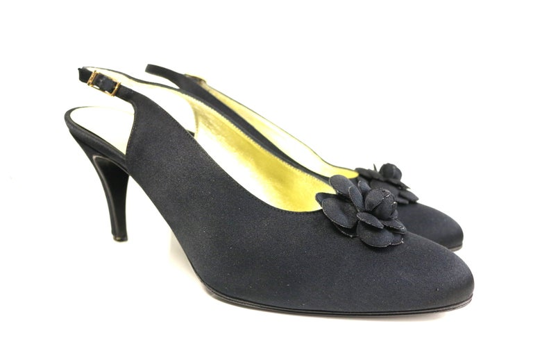 """- Vintage 90s Chanel black silk slingback heels.   - Featuring Chanel signature Camellia in front.   - Gold toned buckle fastening with """"Chanel"""".   - Size 37.5."""