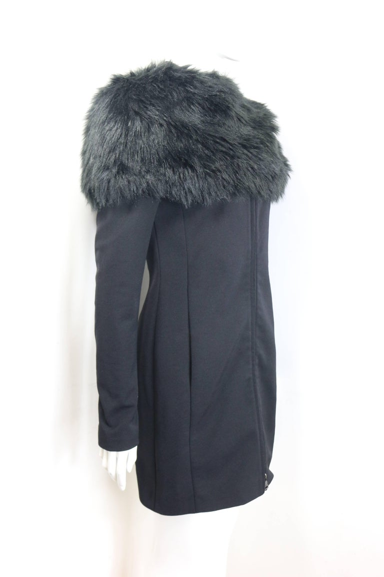 - Prada black nylon knee length jacket.   - Mandarin Collar.   - Two way zippers closure.   - Side pockets.   - Detachable black faux fur.   - Size 38.   - Outer Shell: 70% Nylon, 24 % Polyester, 4% Others. Lining: 57% Viscose, 43% Polyester.