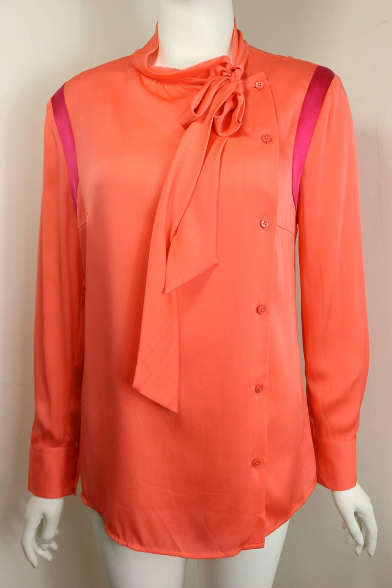 - Ports orange silk button shirt. Pink panels on the shoulder sleeves.   - Featuring collar can be tied as a ribbon. Buttons fastening on the left.   - Size 8.   - 100% Silk.