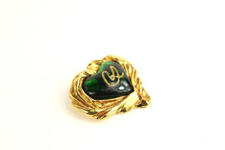 - Vintage 80s Christian Lacroix gold toned setting green gripoix heart-shaped brooch   - Featuring gold written Christian Lacroix logo in the center.   - Length: 2 x 1.7 inches.