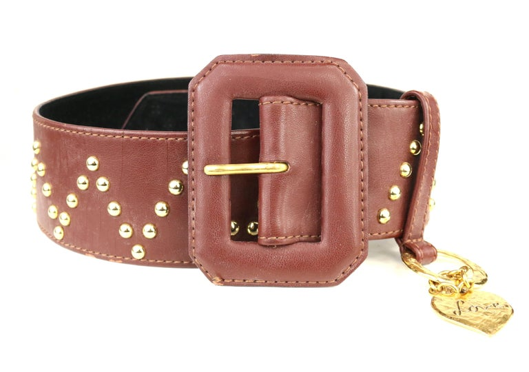 - Vintage Yves Saint Laurent brown leather with V shape gold-toned studs throughout the belt.   - Featuring gold-toned heart shape hardware charm with