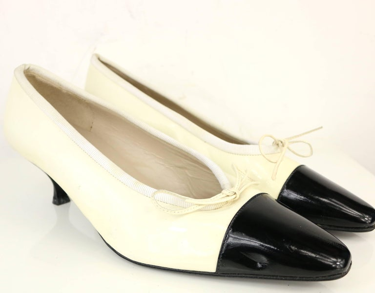 - Vintage 90s Chanel bi-toned black and white patent leather shoes.   - Featuring a tied ribbon in front and low heels.   - SIze 38.   - Condition: Good. Although it has never been worn before, after all these years, it has been slightly discolored