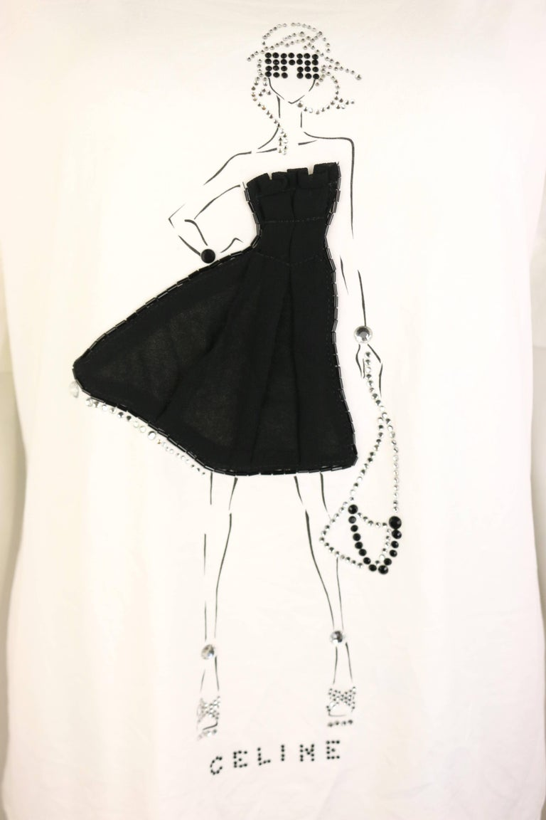 - Celine white with black/silver rhinestones girl print cotton t-shirt.   - Featuring the girl print wears a black tube top fabric dress with black beads and silver rhinestones accessories outline.   - Size XL.   - 90% Cotton, 10% Elastane.