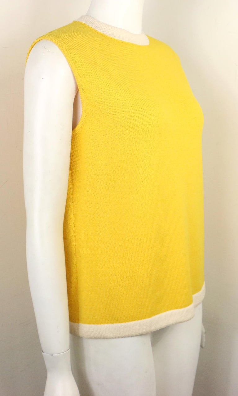 - Vintage 80s St. John yellow cotton sleeveless top. The style is very retro!   - White cotton neck and hem trim.   - Back zip closure.   - Size Small.   - Shoulder: 14 inches. Bust:  32 inches approximately. Length: 23 inches long.