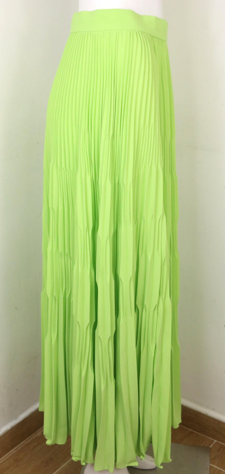 - Vintage 80s Escada green polyester pleated long skirt. Its a really bright and nice color. Pair it with a white t-shirt or top for a hot summer vacation.   - Featuring side zip and button closure.   - Size 36.   - 100% Polyester.   - Unworn with
