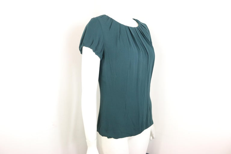 - Celine green silk short sleeves blouse. Inserted drawstring on the neckline and sleeves to create a flowy and pleated effect.   - Featuring a side zip closure. Tiny hook fastening at the back with drawstrings attached.   - Size 38.   - 100% SIlk.