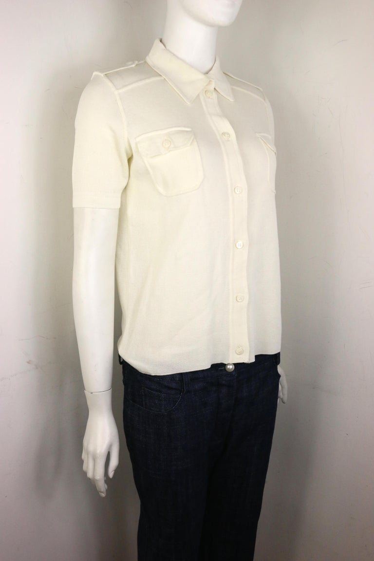 - Vintage 90s Prada white cotton knitted short sleeves collar shirt. The style is fitted.   - Featuring shoulder epaulettes with button closure. Front buttons closure. Two front pockets with button closure.   - Size 44.   - 100% Cotton.