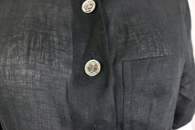 - Vintage 90s Chanel black linen short sleeves collar shirt.   - Featuring two different kinds of silver-toned buttons fastening. One is written