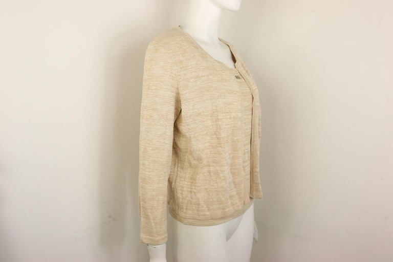 - Vintage Chanel beige cotton and rayon cardigan from spring 1999 collection.   - No button closure.   - Ribbed collar, hem, and cuff.   - Size 40.   - 50% Cotton. 45% Rayon. 5% Polyester.