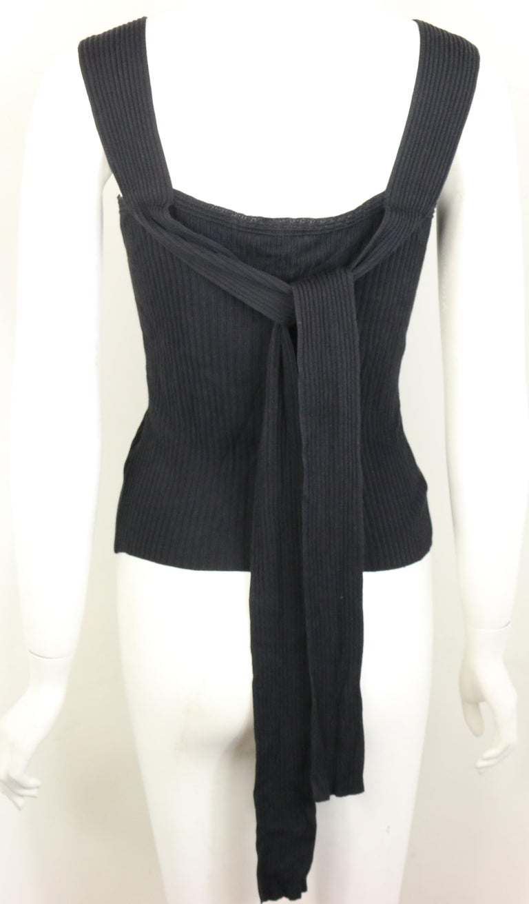- Vintage Chanel black knitted cotton and rayon sleeveless top from the year 1999 spring collection.   - Featuring extended straps fabrics at the back.   - Front slit hem.   - Size 38.   - 33% Cotton, 63% Rayon.