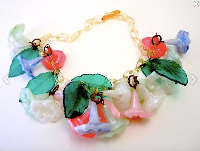 """This vintage deco necklace features multi-color celluloid flowers. It is amazing that it has survived all these years and is in such lovely condition. This piece measures 15"""" and a leaf is 1 3/8"""" x 7/8""""."""