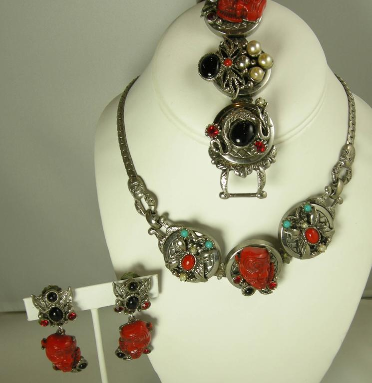 "This very rare set is by Selro. The necklace features the famous red devil design with three charms. It has faux coral, as well as red, white, black cabochon stones accentuated with red crystals. The necklace chain measures 19"" x 1/4"" with the each"