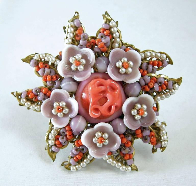 """This vintage 1940s signed Miriam Haskell brooch pin features an ornate floral design with coral, lavender glass beads and seed faux pearls in a gold-tone setting.  In excellent condition, this pin measures 2-1/2"""" in diameter with a c-pin clasp and"""