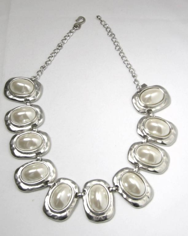 "This signed Kenneth Jay Lane necklace features cabochon cut white faux pearls in a silver-tone setting.  In excellent condition, this necklace measures 20"" long with an adjustable hook closure x 1 1/2"" and is signed ""Kenneth Lane""."