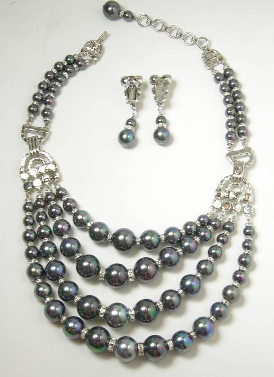 This is a one-of-a-kind Robert Sorrell creation.  It is a bib necklace made with faux Tahitian pearls and crystals in a rhodium silver tone finish.  There are four rows of the Tahitian pearls that graduate in size with crystals in-between.  The