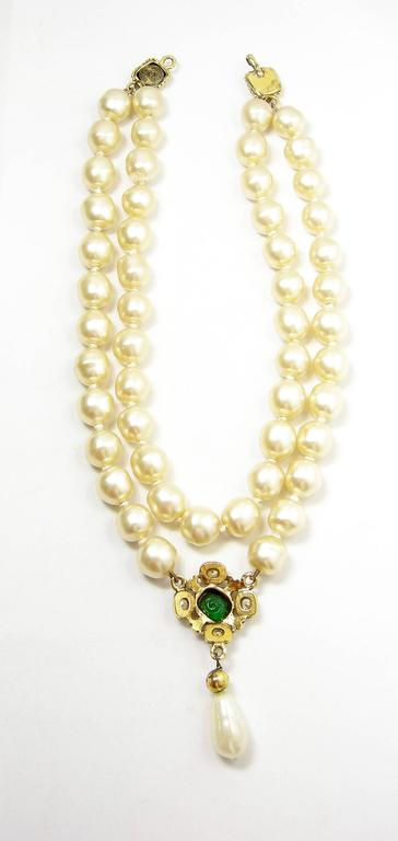 This beautiful 1985 Chanel pearl necklace has a double strand of simulated pearls with a green Gripoix center drop and teardrop pearl at the bottom.  The drop has an oval green Gripoix center set in a gold tone border with the double Cs and crystals